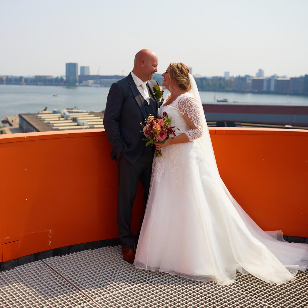 Bruidspaar buiten open een groot balkon
